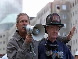 NEW YORK, NY - SEPTEMBER 14: US President George W. Bush (L), standing next to retired firefighter Bob Beckwith, 69, speaks to volunteers and firemen as he surveys the damage at the site of the World Trade Center in New York in this 14 September 2001 file photo. Bush was presented with the same bullhorn he used to address the rescue workers in this photo at a ceremony 25 February 2002 in the Oval Office of the White House in Washington, DC which was attended by Beckwith and New York Governor George Pataki. The President said the bullhorn would be put on display at his father's Presidential Library. (Photo credit should read PAUL RICHARDS/AFP/Getty Images)